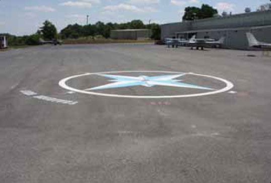 Figure 10-140. The compass rose on this airport ramp can be used to swing an aircraft magnetic compass.